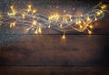 Christmas warm gold garland lights on wooden rustic background. filtered image with glitter overlay Royalty Free Stock Photo