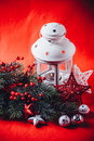 Christmas white lantern is standing with a burning candle in it with a fir tree branch and knit stars on a red background. Royalty Free Stock Photo