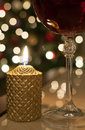 Christmas wine burning candle and a glass of red with glittering tree lights in the background Stock Images