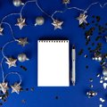 Christmas, winter composition. Notebook with isolated white page, open diary, sketch book mock-up scene on blue surface Royalty Free Stock Photo