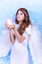 Christmas wish of an angel cute on blue snowy background adorable girl with candle in hands religious winter holiday peace and Royalty Free Stock Images