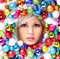 Christmas woman with colored balls face of beautiful girl fashion makeup and shiny baubles Stock Image