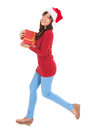 Christmas woman running with gift box beautiful and holding wearing santa hat standing in full body isolated on white background Royalty Free Stock Photos