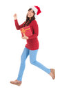 Christmas woman running with gift and holding wearing santa hat standing in full body isolated on white background smiling Stock Images