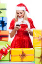 Christmas woman texting message with phone surrounded by presents isolated on white background Royalty Free Stock Image