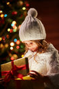Christmas wonder little girl in white winterwear looking at present in golden giftbox with red ribbon Royalty Free Stock Images