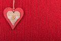 Christmas wooden decoration heart on red wool fabric. Christmas rustic background with copy space Royalty Free Stock Photo