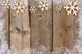 Christmas wooden snowflake top border with snow frame on wood Royalty Free Stock Photo