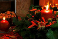 Christmas wreath festive decorated with red candles bows and presents and nuts in front of a lively fire Stock Images