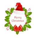 Christmas wreath with holly sweets santa hat and red bow on white background Stock Photos