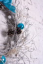 Christmas wreath made ​​of branches with cones and balls on a white wall Royalty Free Stock Photos