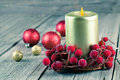 Christmas wreath from red berries with a candle on wooden background Stock Photo