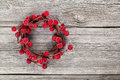 Christmas wreath from red berries on wooden background Royalty Free Stock Photos