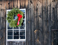 Christmas wreath with red bow on barn Stock Photography