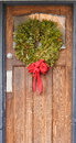 Christmas wreath with red ribbon on old wood door an a green tree Royalty Free Stock Photography