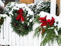 Christmas wreath in snow with red ribbon hanging on white picket fence and covered with Royalty Free Stock Images