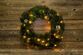 Christmas wreath with white lights on rustic wooden boards Royalty Free Stock Photo