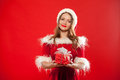 Christmas, x-mas, winter, happiness concept - smiling woman in santa helper hat with gift box, over red background Royalty Free Stock Photo