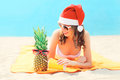 Christmas young smiling woman in red santa hat with pineapple cup fresh fruit juice lying on beach over blue sea Royalty Free Stock Photo