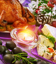 Christmastime banquet festive table setting with bright candle light new year eve tasty baked chicken black olives pine cone with Stock Image