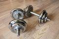 Chrome dumbells on wooden floor Royalty Free Stock Photos