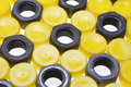 Chrome steel nuts and yellow plastic caps Royalty Free Stock Photo