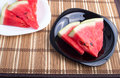Chunks of juicy red watermelon on black and white plate Royalty Free Stock Photo