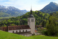 Church and alps mountains gruyeres switzerland beautiful landscape with fields in Royalty Free Stock Image