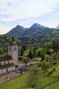 Church and alps mountains gruyeres switzerland beautiful landscape with fields in vertical image Stock Photography
