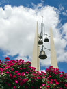 Church bells against bright blue sky clouds and red roses these tall chruch cross steeple stand out a rich with puffy white deep Royalty Free Stock Image
