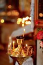 Church candles in the on a background of lights candlestick with burning and a bouquet of roses Stock Photo