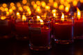 Church candles in red transparent chandeliers Royalty Free Stock Photo