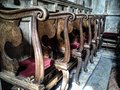 Church chairs or benches inside a church. The chairs are decorated with rich wood carvings and equipped with a soft seat of red
