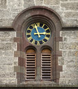 Church clock detail of a round black and blue and golden with roman numerals in a facade of brown and gray stones taken at the Royalty Free Stock Photos