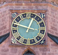 Church clock detail of a round black and golden with roman numerals in a red facade taken at the town in freudenstadt Royalty Free Stock Photography