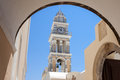 Church clock tower fira santorini a framed by an arch in greek island of Royalty Free Stock Photo