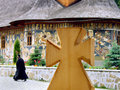 Church cross wooden and moldavian traditional in romania with monk in background Royalty Free Stock Photo