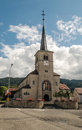 Church decorated with flowers in switzerland is an image vertically mountains in the background on a cloudy day Royalty Free Stock Images