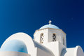 Church and dome in santorini greece white against blue sky looking up moon is visible to the right island cyclades Royalty Free Stock Image