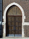 Church door chursh doors set in a red brick sturcture with a drain pipe on the side Royalty Free Stock Photos