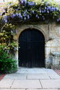Church door entrance an old english and with unusual and ancient stonework surrounded by beautiful flowers Royalty Free Stock Images