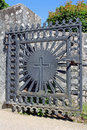 Church gate with a cross old iron and granite wall at the entrance to at summer Stock Image