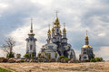 Church with golden domes on the background of thunderclouds Stock Photography