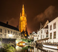Church of Our Lady and bridge over water canal by night, Bruges, Belgium