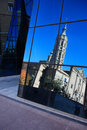 Church reflection modern glass wall with of old against blue sky Royalty Free Stock Image
