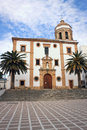 Church in ronda spain the centre of with courtyard with palm trees and cloudy blue sky Royalty Free Stock Photo