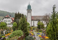 Church stein am rhein switzerland a typical with a baroque curved green bronze tower and a cemetery with blooming flowers Royalty Free Stock Photography