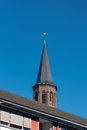 Church tower behind appartment house with weathercock before blu blue sky Stock Images