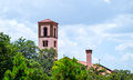 Church towers with trees in foreground and cloudy sky Royalty Free Stock Photo