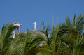 Church with white cross blue sky and palm trees in tropics Royalty Free Stock Images